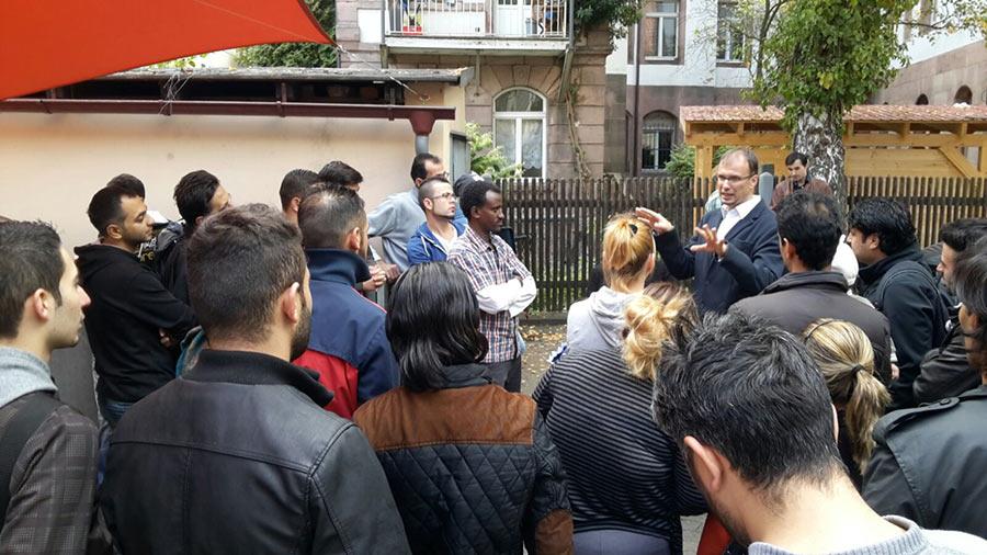 Pastor Moser begrüßt Flüchtlinge aus Syrien im Gospelzentrum am 27.09.15